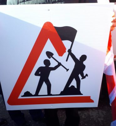 construction site sign, worker breaking out waving flag